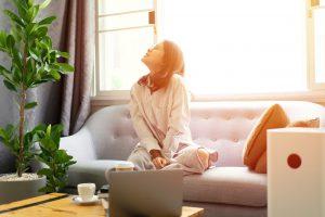 Kobieta wykorzystująca filtrowanie powietrza w domu za pomocą oczyszczacza powietrza.